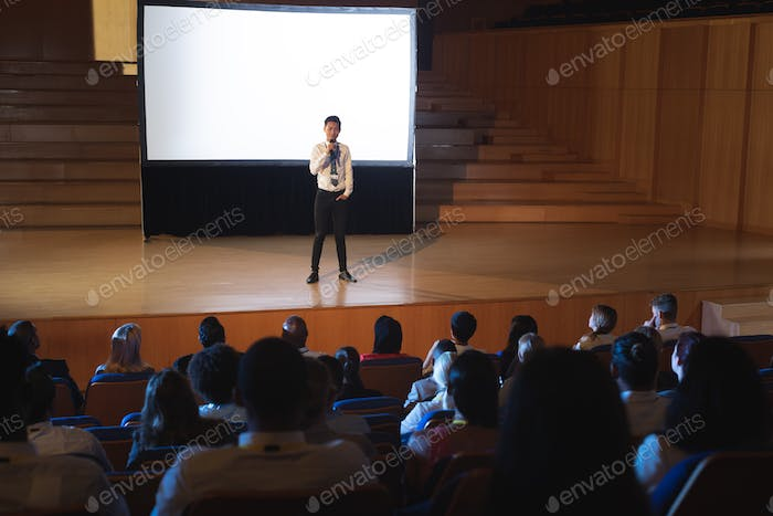 Businessman standing and giving presentation in auditorium while holding mike in his hand