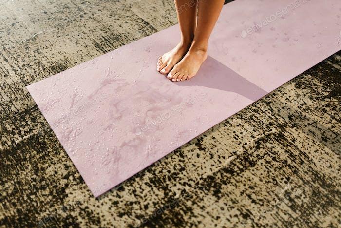 Female legs standing on wet yoga mat