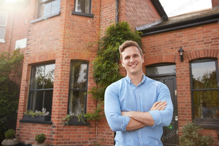 Portrait Of Excited Man Standing Outside New Home Holding Keys