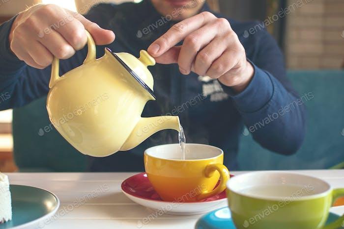 Manshand mit einer gelben Teekanne gießt Kräutertee in eine Tasse. Teezeit im Café, Tea Party