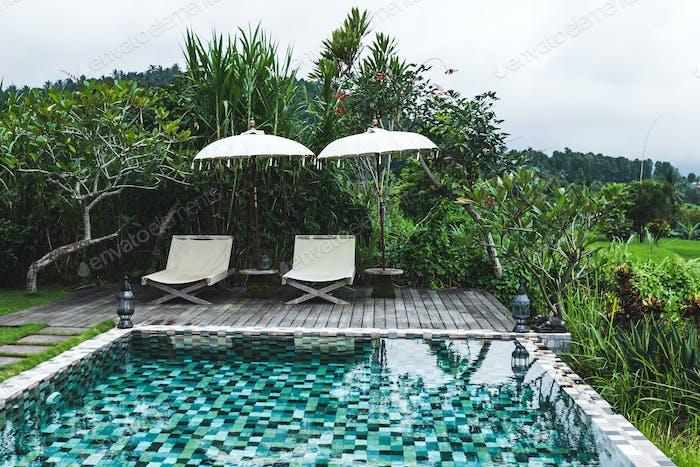Blick auf den Pool mit zwei Chaiselongues und weißen Sonnenschirmen im Bali-Stil