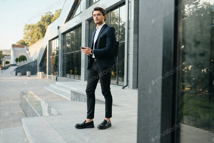Stylish man in classic suit with cellphone thoughtfully looking aside outdoor next to glass building