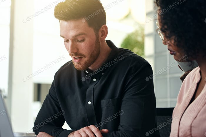 Two focused businesspeople talking together at an office desk