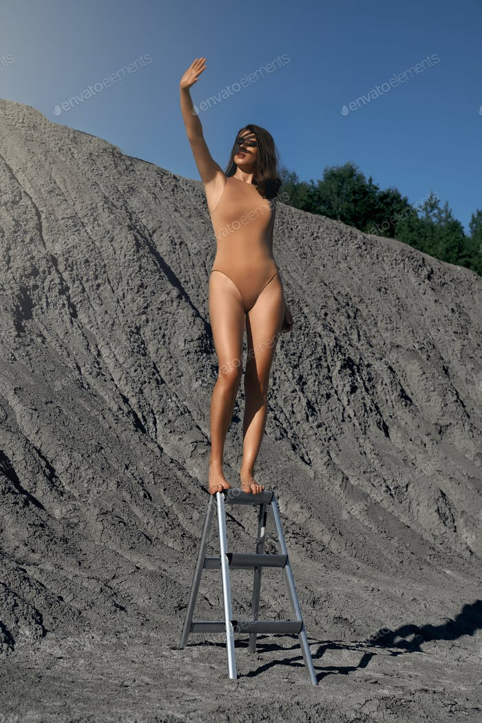 Woman wearing body posing on ladder in quarry