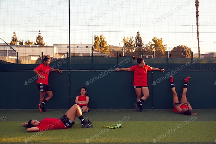 Portrait Of Womens Football Team Relaxing After Training For Soccer Match On Outdoor Pitch