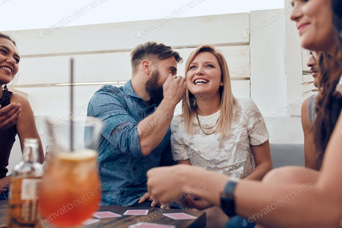 Man sharing a secret with woman in a party