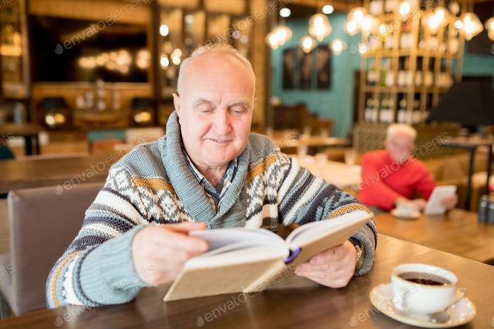 Curious chubby man reading interesting book in cafe