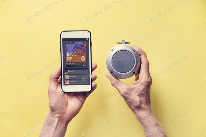Hands holding smartphone connect to bluetooth speaker