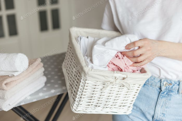 Wicker rustic basket with washed clothes in woman's hand ready to ironing