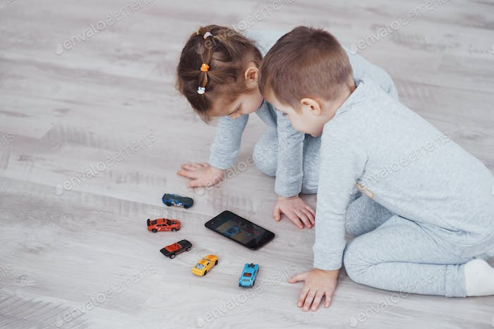 Children using digital gadgets at home. Brother and sister on pajamas watch cartoons and play games