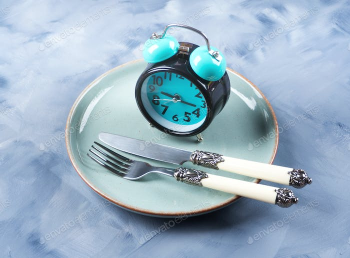 Intermittent fasting concept with blue alarm clock