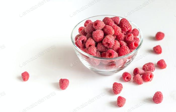 Fresh raspberries in the glass bowl