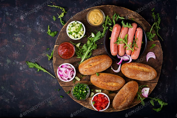 Ingredients for hot dog with cucumber, tomato and red onion on wooden background. Top view. Flat lay