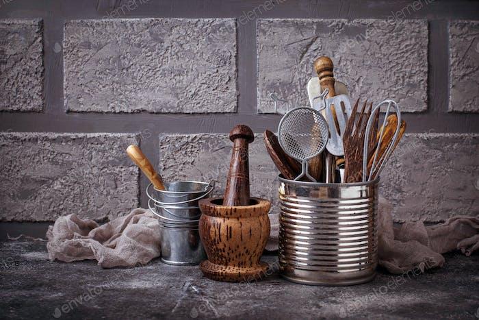 Kitchen utensils on brick wall background