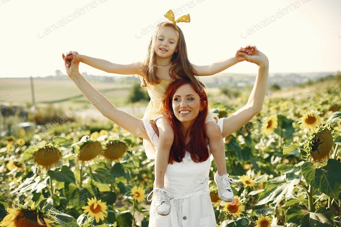 Beautiful and cute family in a field wirh sunflowers