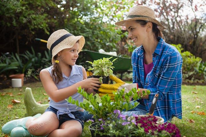 Lächelnde Tochter und Mutter mit Topfpflanzen