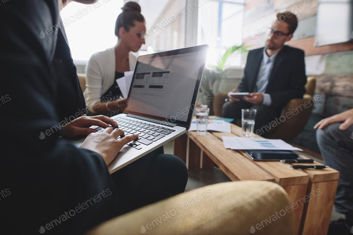 Businesswoman working on laptop during meeting