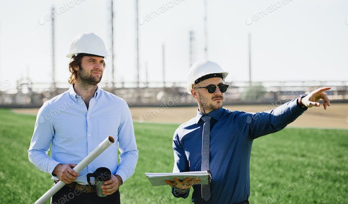 Two young engineers with hard hat standing outdoors by oil refinery, discussing issues