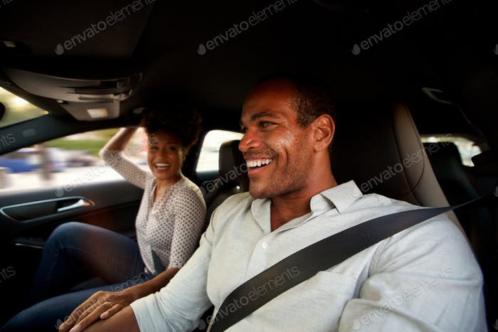 Portrait of man and woman sitting together in automobile smiling