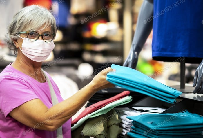 Attractive senior woman wears protective face mask due to coronavirus chooses new t-shirts in store