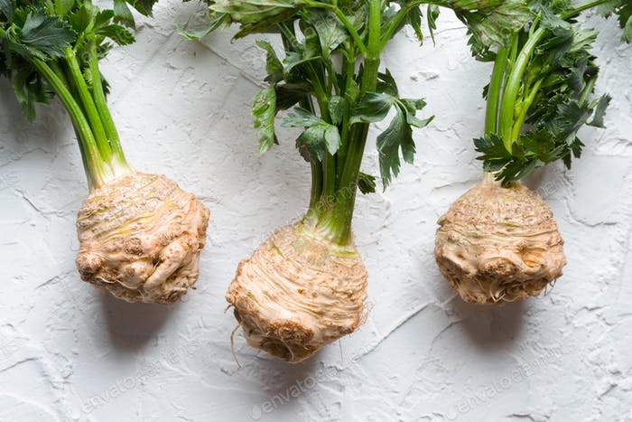 Celery roots with green leaves on a white table