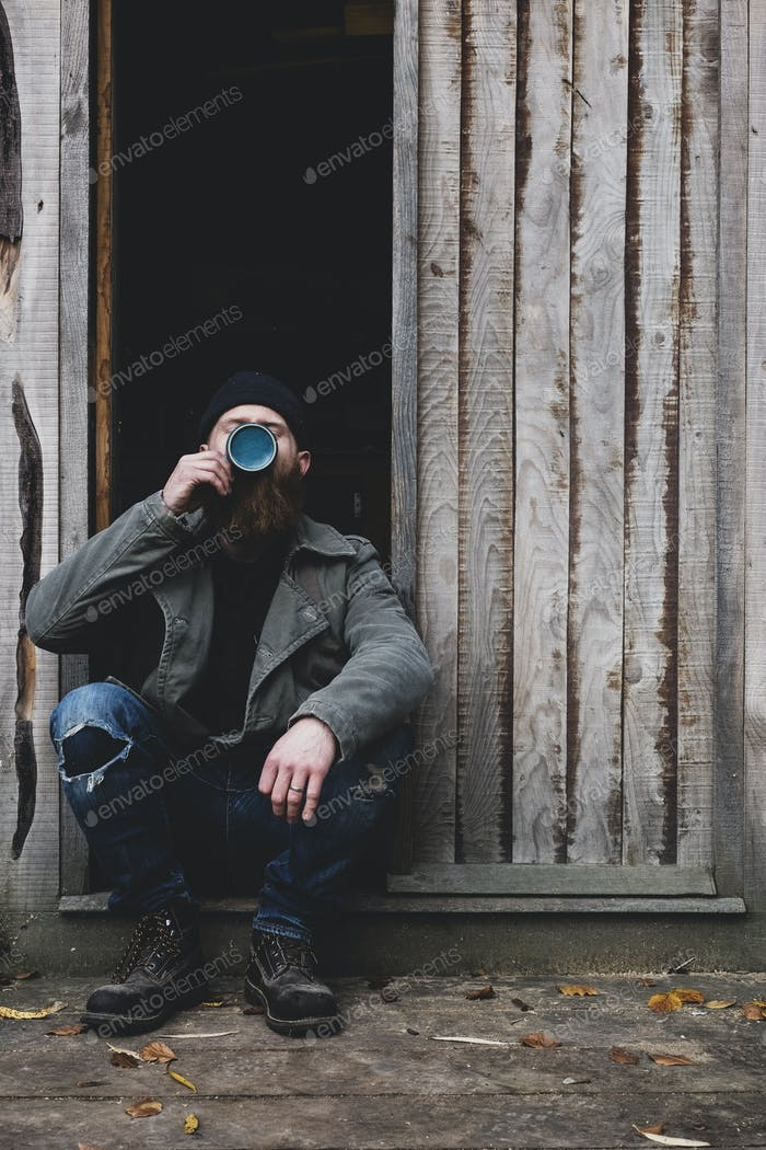 Bearded man sitting in doorway of wooden workshop, drinking tea from blue mug.
