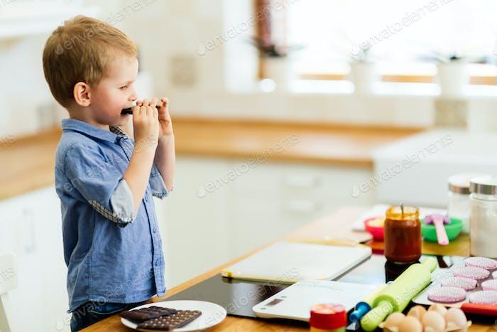 Child tasting chocolate bar in kitchen