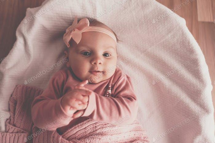 Little cute baby girl lying in basket