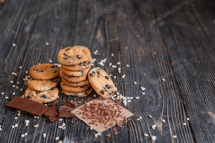 Homemade Chocolate Chip Cookies with crushed chocolate crumb on dark rustic table