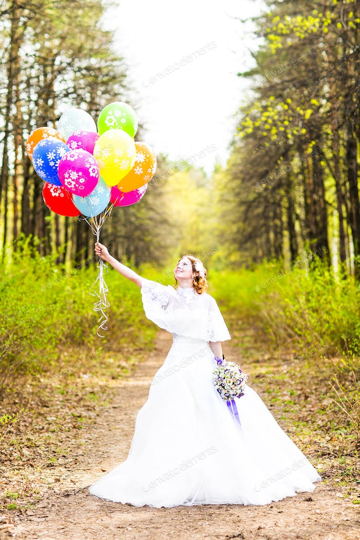 Cheerful bride with bunch of balloons outdoor