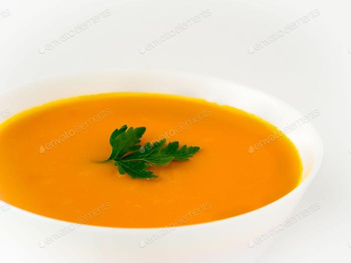white bowl of pumpkin soup