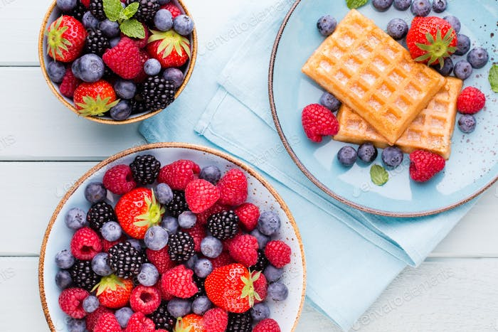 Fresh berries salad in a plate on a  wooden background.