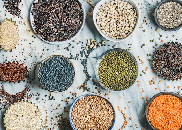 Various raw uncooked grains, beans, cereals, marble background, top view
