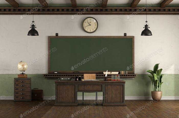 Retro style empty classroom with blackboard and desk teacher's desk
