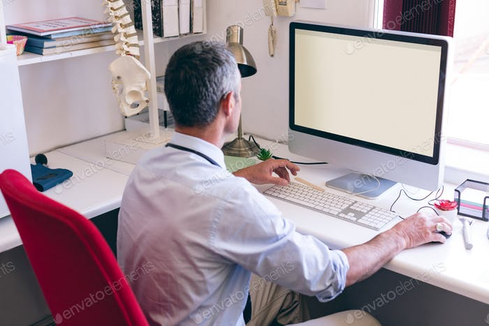 Rear view of confident Caucasian male doctor working on computer at clinic of retirement home