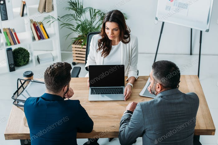 advisor showing to investors laptop with copy space at workplace