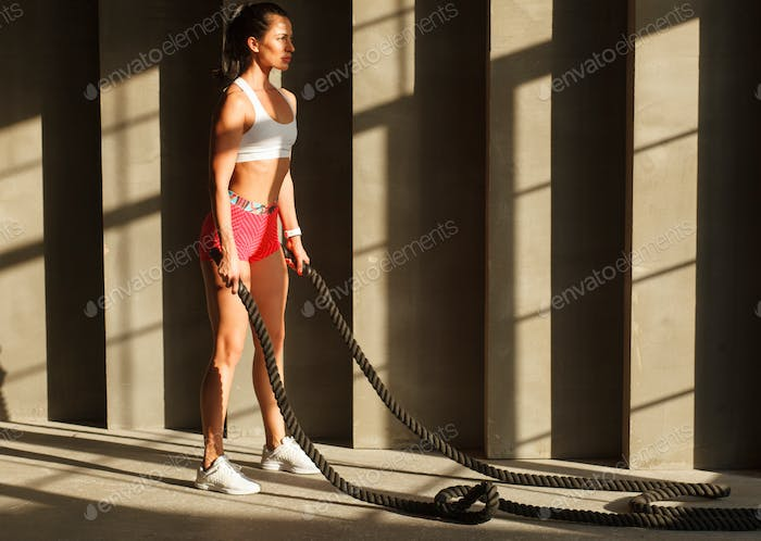 sportswoman ready to crossfit workout with battle rope