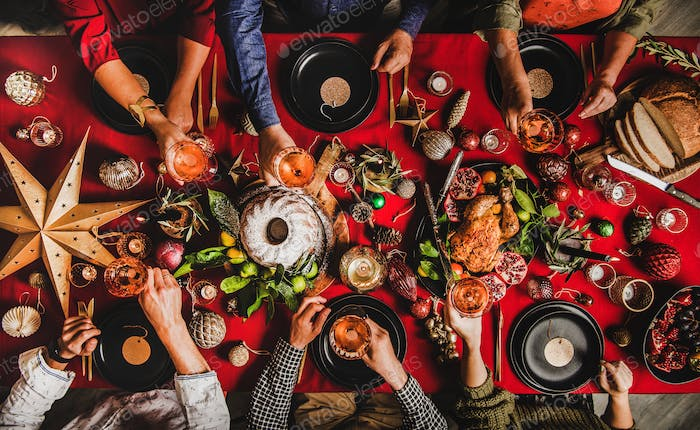 Christmas or New Year party. Flat-lay of people feasting at decorated table
