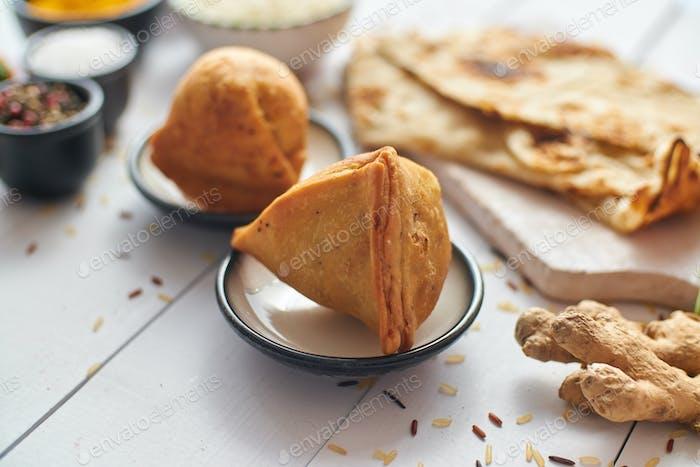 Traditioneller Indian Food Snack Samosa serviert auf einem Teller auf einem weißen Holztisch