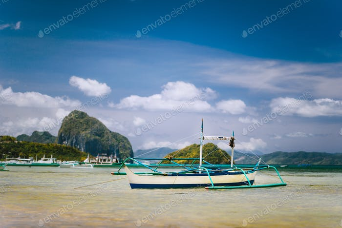 Traditional banca fishermen boat in shallow lagoon on Corong Beach. Nido, Philippines. Blue sky and
