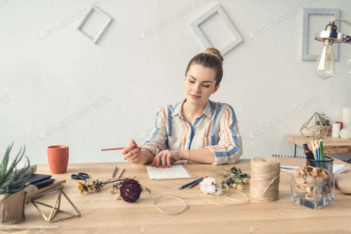 привлекательный женский декоратор, работающий за столом с сухими цветами