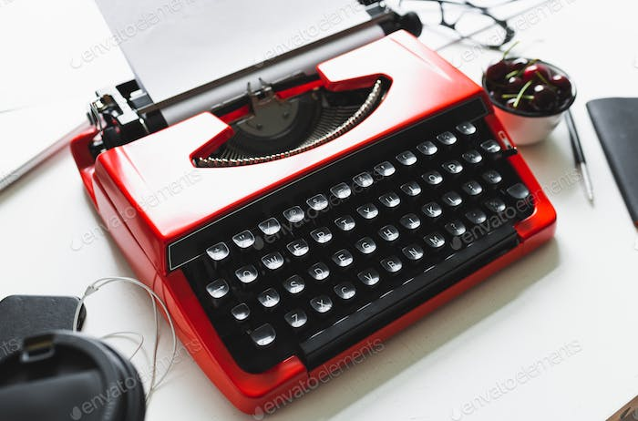 Workplace with bright red vintage typewriter