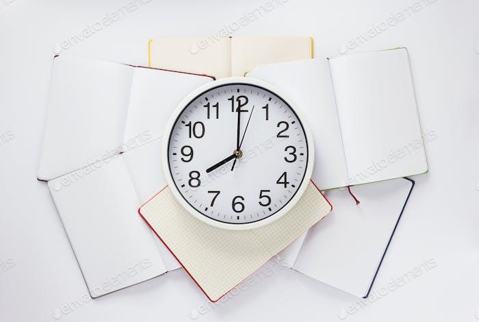 offenes Notizbuch und Uhr auf weißem Hintergrund