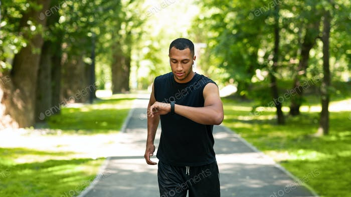 Attractive black guy looking at his fitness tracker while jogging at park