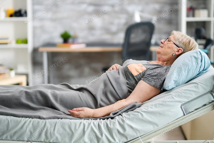 Old granny sleeping in a modern nursing home room