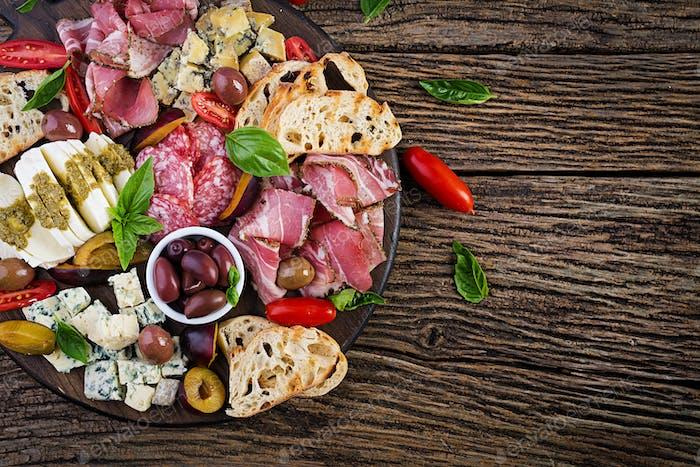 Antipasto platter with ham, prosciutto, salami, blue cheese, mozzarella with pesto