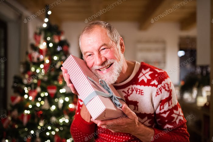 Senior man in front of Christmas tree holding a gift.