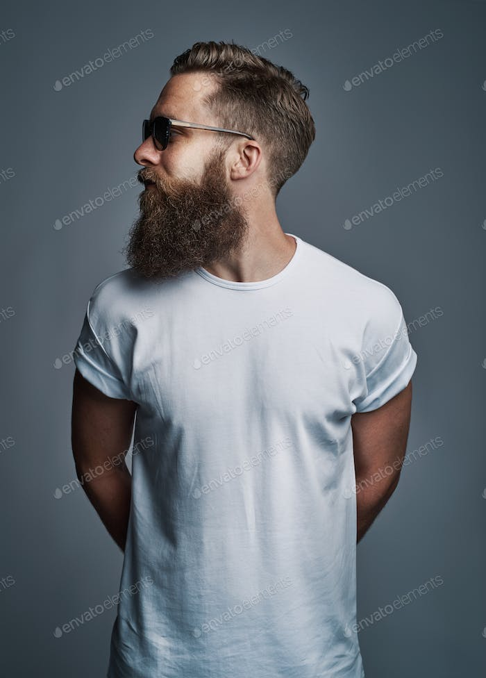 Stylish young man with a beard wearing sunglasses looking sideways