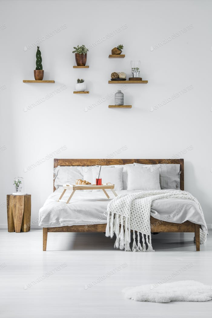 Front view of a wooden framed double bed with linen, pillows and