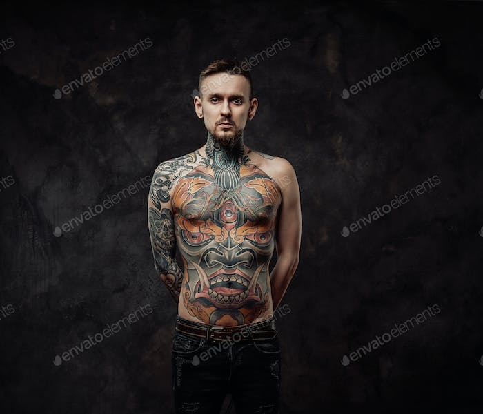 Naked tattooed hipster poses in dark background looking at camera